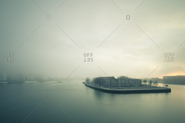 Buildings on island shrouded in fog on the Nieuwe Maas river in Rotterdam, Netherlands
