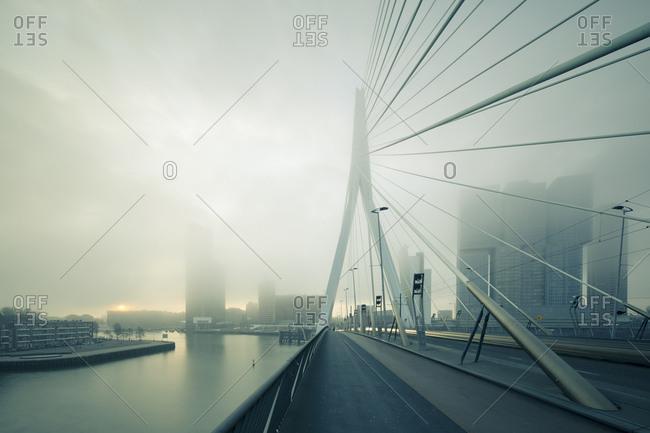 Looking along Erasmus Bridge at apartment blocks on banks of Nieuwe Maas river hidden in fog