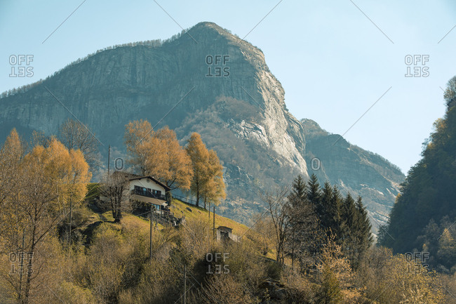 Looking up slope at isolated farm house with rocky mountain top in background in Valle die Verzasca, Switzerland