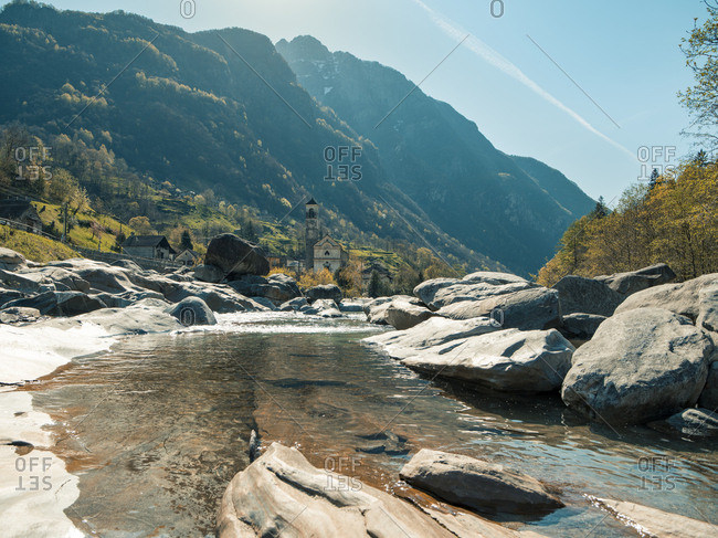 Looking along small rocky river towards village of Lavertezzo in Valle die Verzasca, Switzerland