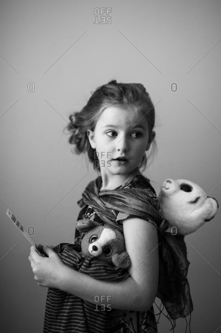Young girl carrying stuffed animals in black and white