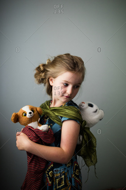 Young girl carrying stuffed animals