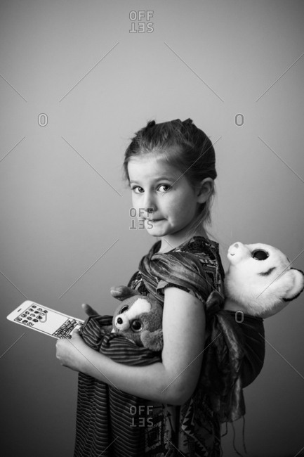 Young girl carrying stuffed animals wrapped in a scarf