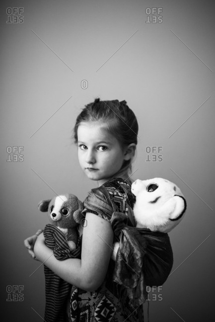 Little girl carrying stuffed animals wrapped in a scarf