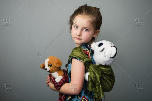 Little girl carrying stuffed animals