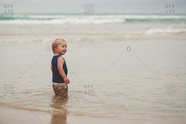 Blonde toddler boy standing in shallow waves at the beach