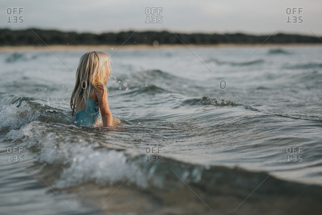 Girl swimming in the ocean at sunset