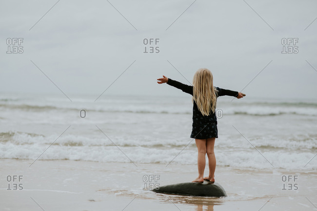 Back view of blonde girl standing on a rock on the beach