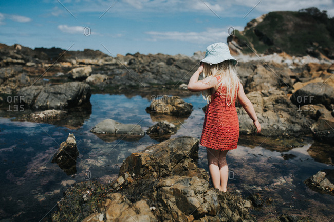 Girl in hat playing in rock pools in Australia