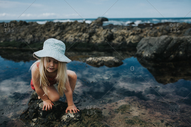 Girl crawling over rocks in shallow pool by the beach