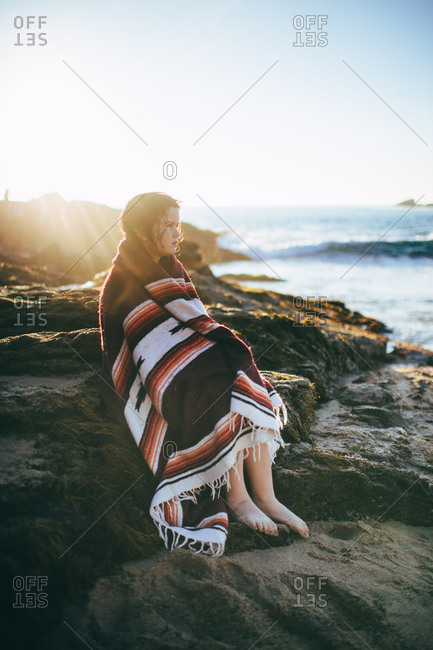 Young girl drying off with blanket on rocky beach at sunset
