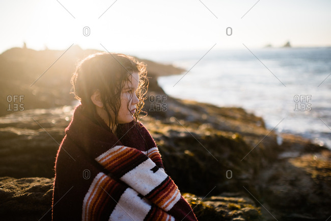 Portrait of brunette girl wrapped in blanket at golden hour on the beach