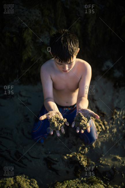 Overhead view of brunette boy holding clumps of wet sand on the beach