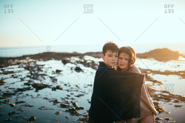 Siblings drying off together on muddy beach at sunset