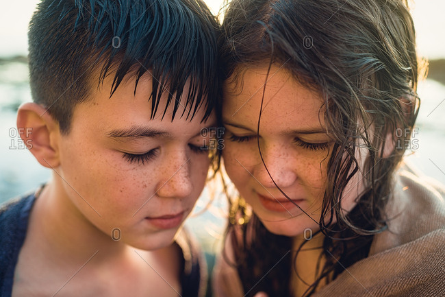 Portrait of brother and sister on beach with wet hair