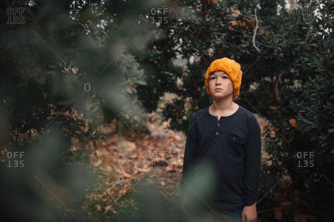 Adolescent boy wearing handmade hat standing alone in wooded area