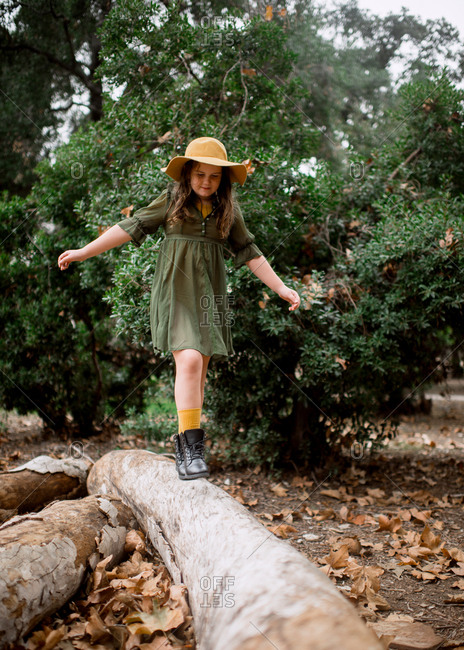 Girl with felt hat and leather boots balancing across fallen log in forest