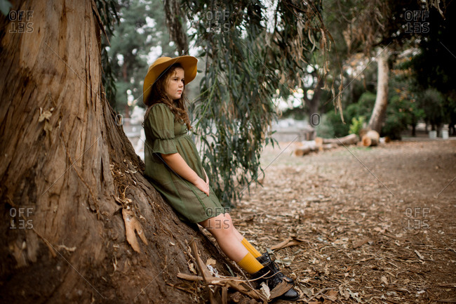 Thoughtful tween girl posing against thick tree trunk in the park