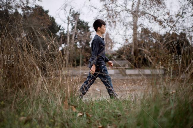 Boy walking alone through overgrown field
