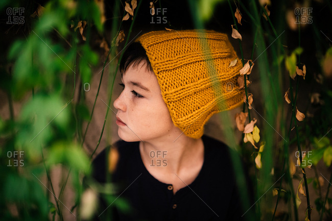 Thoughtful boy in knit hat looking to side in garden