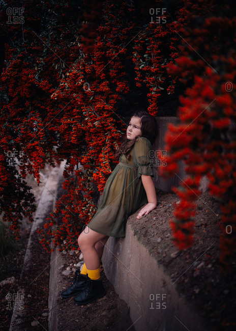 Quiet girl leaning against stone wall surrounded by vibrant berries
