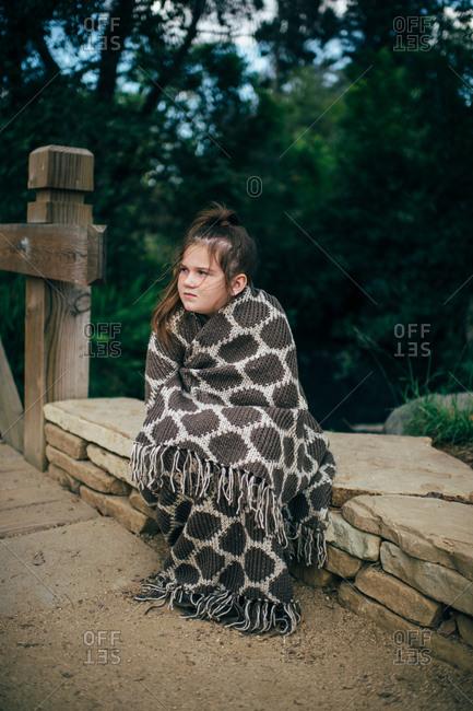 Girl sitting on rocks wrapped in blanket outside
