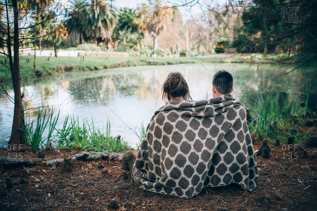 Siblings sitting in front of pond sharing thick woven blanket