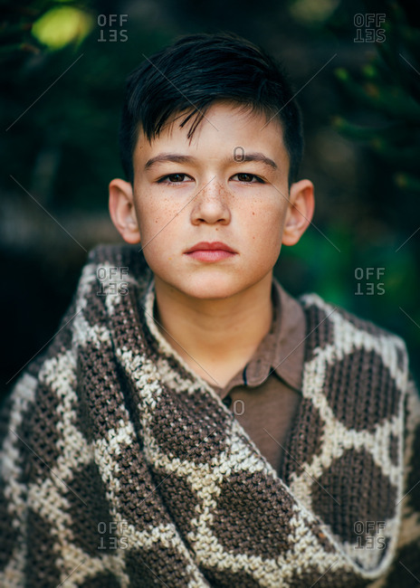 Brunette adolescent boy stranding outside with thick knit blanket