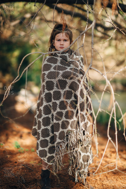 Girl in ponytail staring with patterned blanket wrapped around her in woods