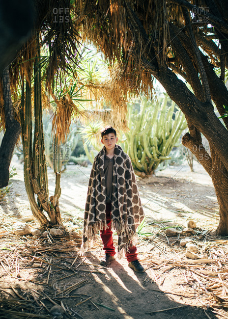 Boy standing along in shade with woven blanket