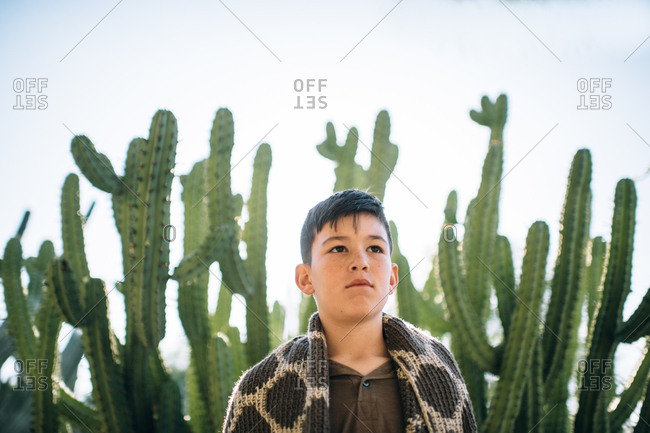 Adolescent boy standing in front of cacti with blanket