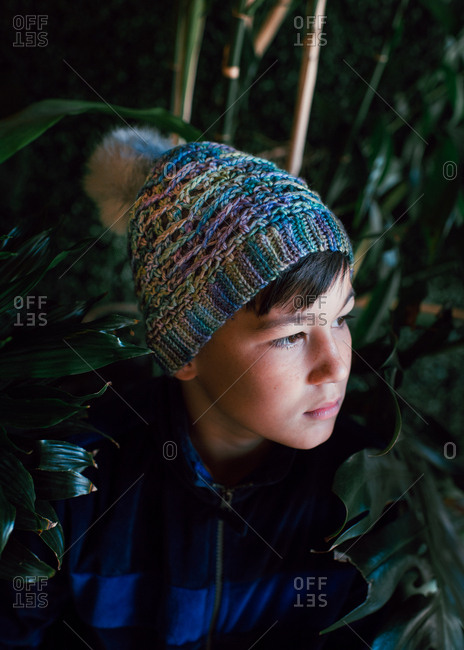 Pensive boy in winter clothes staring off to side outside