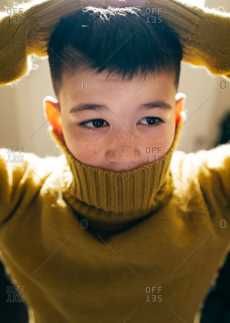 Boy in turtleneck sweater covering lower part of face