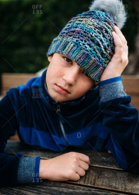 Moody boy sitting at picnic table in knit hat
