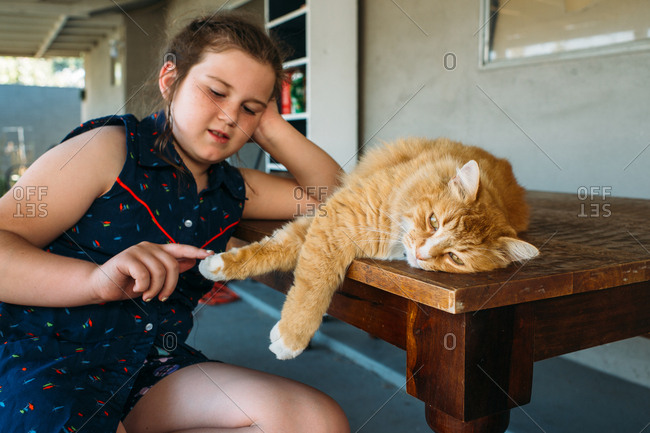 Girl petting cat outside on wooden table