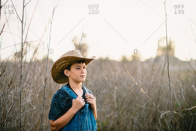 Boy in cowboy hat and overalls in dry field