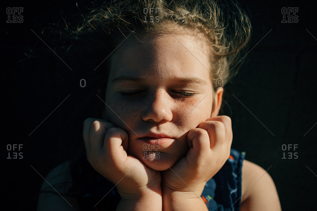 Close-up portrait of girl with eyes closed resting chin in hands