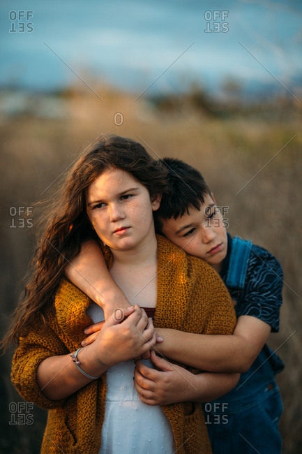 Siblings standing together in field at golden hour