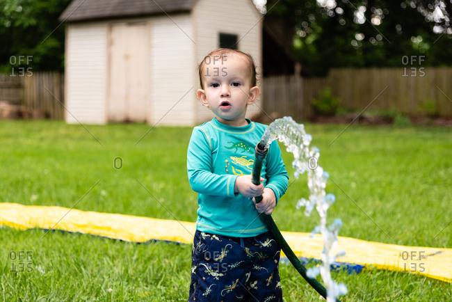 Young boy in swim wear spraying water with hose in backyard