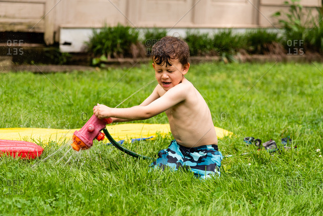 Young boy in swim shorts looking surprised as sprinkler sprays him in face in backyard