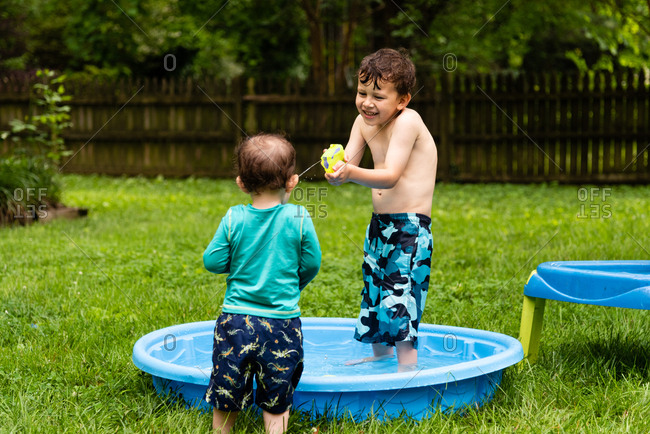 Young boy squirting brother in face with water from squirt gun