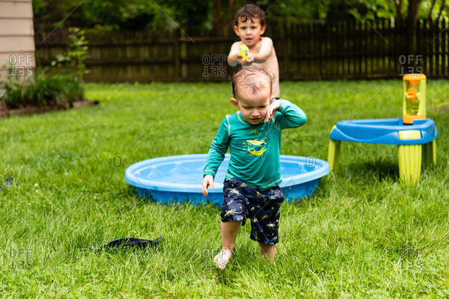 Little boy walking away as older brother sprays him with water from squirt gun
