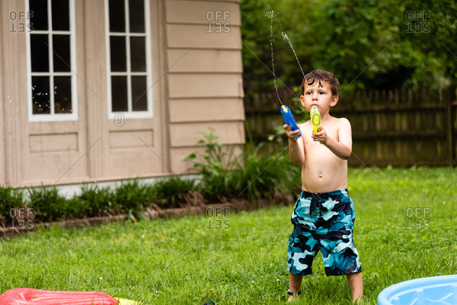 Young boy shooting water from squirt guns into the air in backyard
