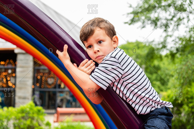 Young boy looking worried and hanging onto climbing frame at playground