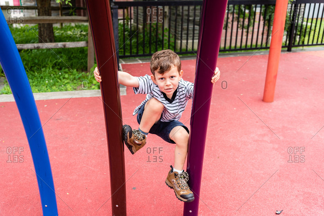 Young boy looking confident as he starts climbing up playground equipment