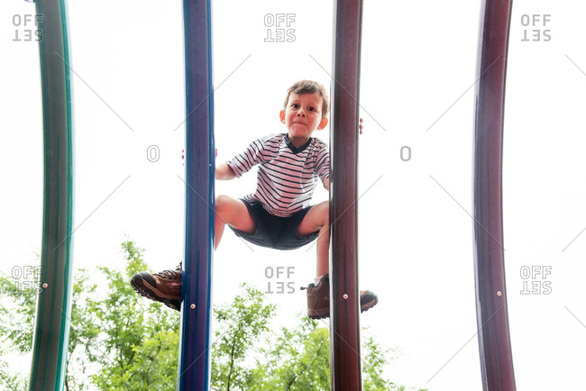 View from below of small boy climbing on parallel bars in playground