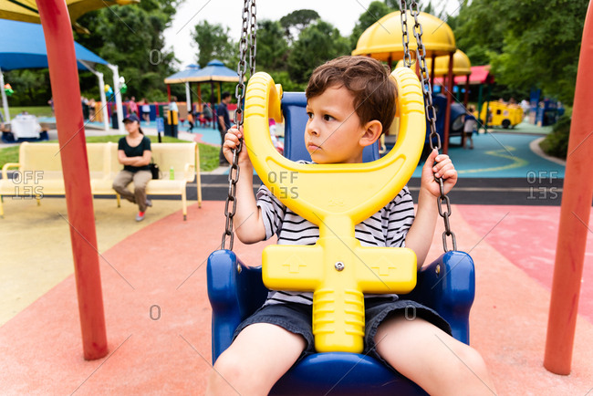 Small boy looking trapped in child's swing with safety bar