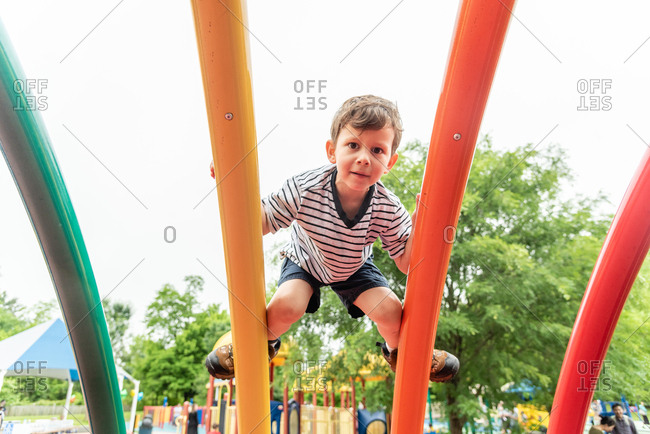 Small boy making his way up climbing frame in playground