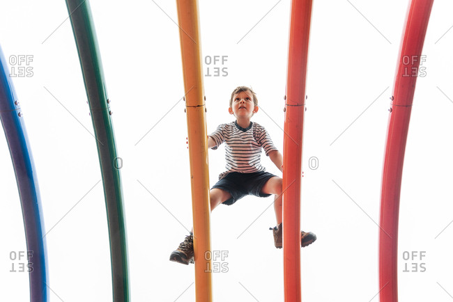 Low angle view of small boy making his way over top of climbing frame in playground