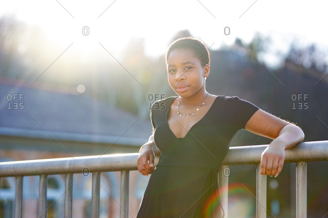 Portrait of a young adult woman leaning against railing